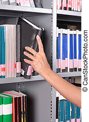 hand removing book - hand removing or replacing a book on a...