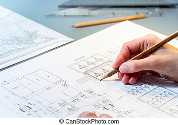 Macro close up of quantity surveyors hand reviewing technical drawing.
