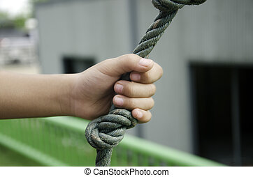 Hand rope. - Child's hand holding a rope in the grass.