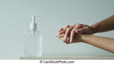 Hand sanitizer alcohol gel rub clean hands hygiene prevention of coronavirus virus outbreak. Woman using bottle of antibacterial sanitiser soap. Slow motion on RED cinema camera.