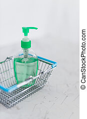 hygiene against viruses and bacteria concept, hand sanitizer bottle inside shopping basket symbol highly sought after products in times of self-isolation and quarantines
