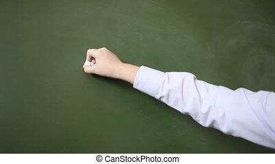 Hand schoolboy writes with chalk on a blackboard