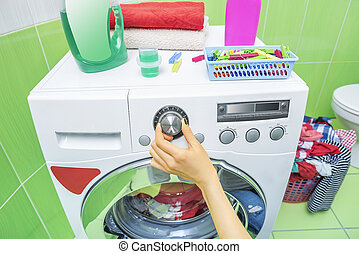 Hand selects the wash mode. - The hand selects the washing...