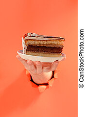 Hand serving a chocolate cake through a torn hole in red paper background.