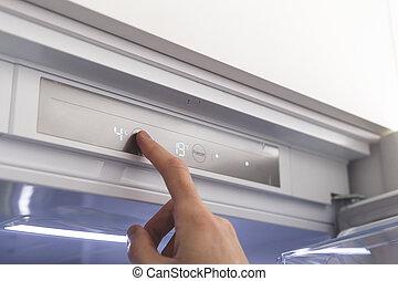 Hand sets temperature of refrigerator