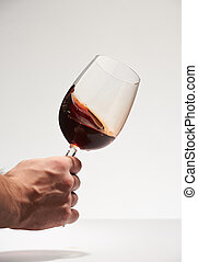 Hand shaking glass with red wine