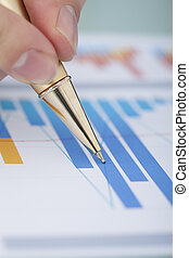 Hand Showing Diagram On Financial Report With Pen