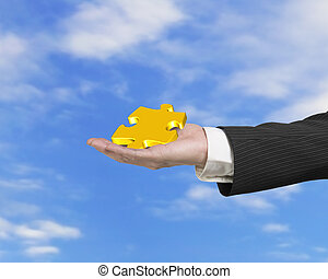 Hand showing gold jigsaw puzzle piece with blue sky clouds