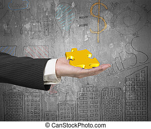 Hand showing gold jigsaw puzzle piece with business concept dood