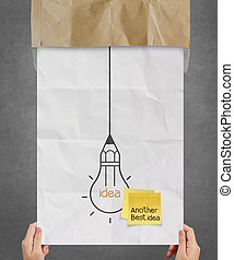 hand showing sticky note with another idea light bulb on crumpled paper as creative concept