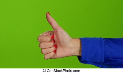 Hand showing thumbs up on green screen background. Sign language