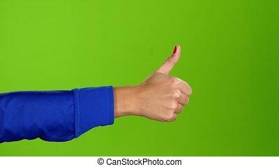 Hand showing thumbs up twice per frame. Greeen screen studio...