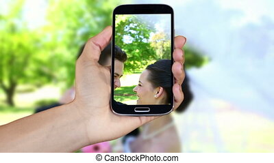 Hand showing wedding clips on smartphone screen montage