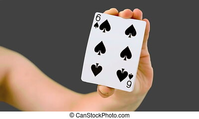 Hand shuffling and pushing cards towards the camera on grey screen