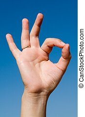 hand signal. Human hand on a blue sky