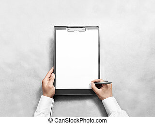 Hand signing blank black clipboard with white a4 paper ...