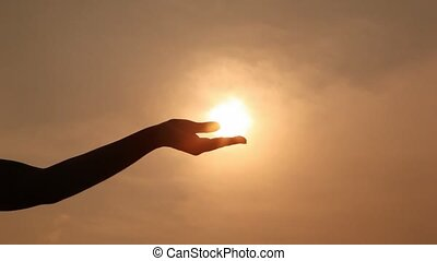 hand silhouette holds sun on palm, compresses and unclenches...