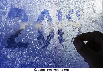 hand silhouette is writing on the frozen window figures 2019. The concept of waiting for the new year. Cold winter theme. First person view.