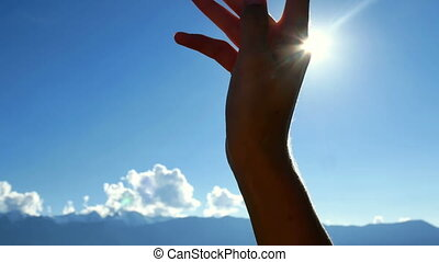 Hand silhouette sun - Hand in silhouette raised up to the...