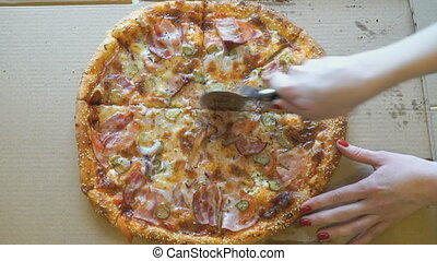 Hand slicing a meat pizza into slices using knife