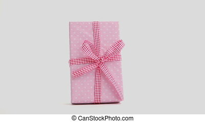 Hand snatching away pink present with gingham ribbon on...