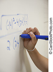 Hand solving an equation on a whiteboard with a blue marker.