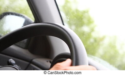Hand spinning wheel man riding in a car, close-up