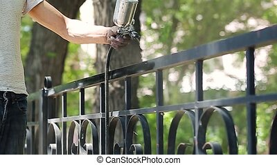 Hand spraying a black paint in slow motion on the fence in...