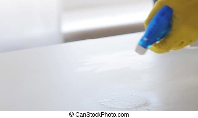 hand spraying cleanser and cleaning table with rag