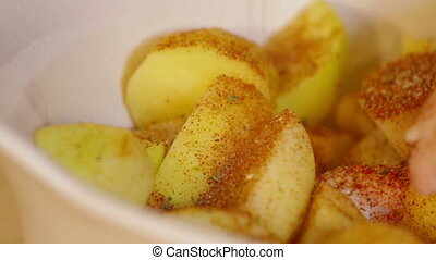Hand sprinkle spices on potatoes. Close up - Hand sprinkle...