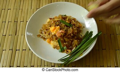 hand squeeze lemon lime on Pad Thai stir fried rice noodles mixed and scooping by fork to eat