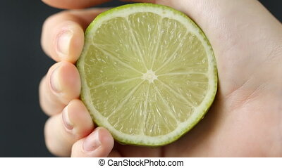 hand squeezing lime on dark background