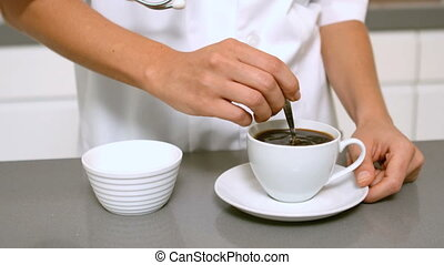 Hand stirring cup of coffee in slow motion