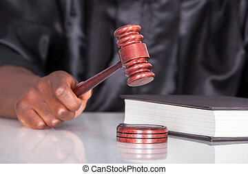 Hand Striking Gavel In A Courtroom