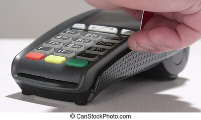 Hand swiping debit card through credit card terminal and entering PIN code