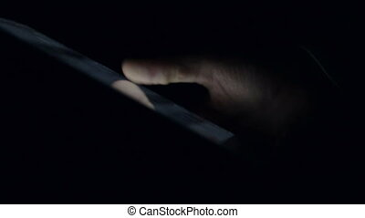 Hand Swiping Tablet searching on shopping website in dark...