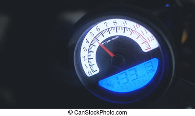 hand switches on engine of motorcycle on control board by speedometer at night