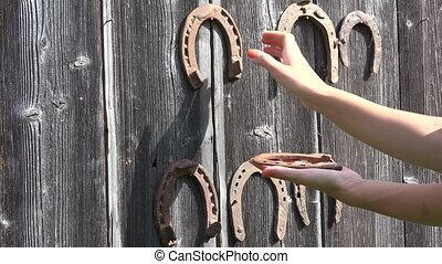 Hand take off retro rusty horseshoes hanging on old wooden...