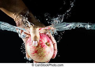 hand take up Apple splashing in water.
