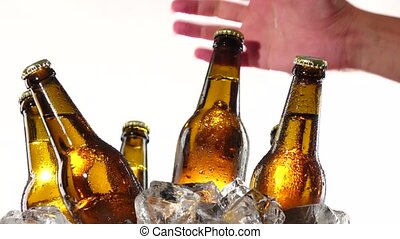 Hand takes a bottle of cold beer. White background . Close up