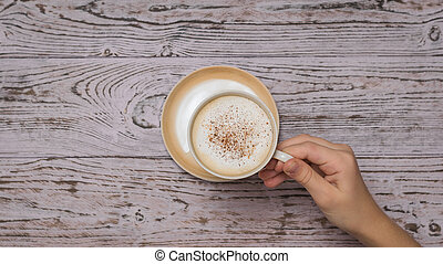 Hand takes a Cup of coffee from the wooden table.