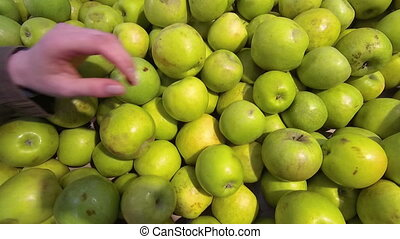Hand takes a green apple in the store