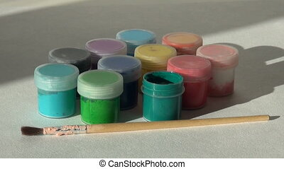 Hand takes, opens and puts jar green Acrylic gouache paint....