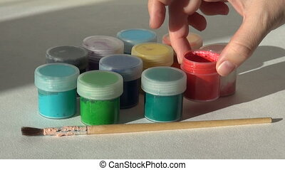 Hand takes, opens and puts jar red Acrylic gouache paint....