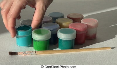 Hand takes, opens and puts jar turquoise Acrylic gouache...