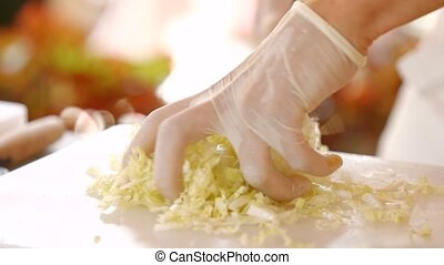 Hand takes shredded chinese cabbage. Pieces of fresh cabbage. Ingredient for vegetable soup. Chef's hands in white gloves.
