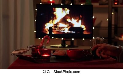 winter holidays and hygge concept - hand taking cup of coffee or hot chocolate from table with ginger cookies, candle, candy canes and gift boxes over tv monitor used as fireplace at cozy home