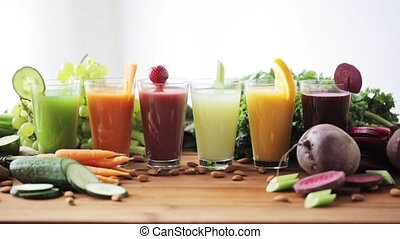 healthy eating, vegetarian food, diet and detox concept - woman hand taking glass of carrot juice from table with vegetables and fruits