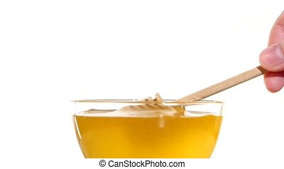 Hand taking honey from bowl using wooden spoon dipper, pit it up, on white, slow motion