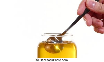 Hand taking honey from glass jar using metal spoon, on white, slow motion